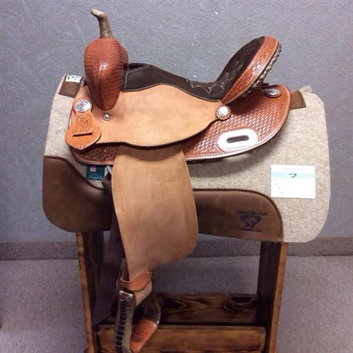 "RS Custom Barrel Saddle - 15"" Seat With a Round Skirt and Basket weave tooling. This saddle is built to be light weight and will fit a short or long backed horse. It has a rough-out jockey and fenders, suede seat, silver laced cantle, and basket weave tooling. (#1039)"