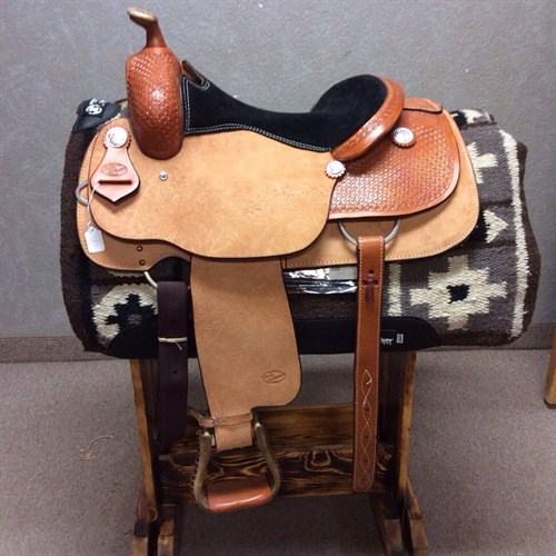"""15"""" Jeff Smith Cowboy Collection Reiner. This beautiful reining saddle features a rough out seat, fenders and jockey with basket weave tooling and conchos to add a little flash.  It is light weight for easy managability and comes with back cinch and rawhide wrapped stirrups.  (CCR-1)"""