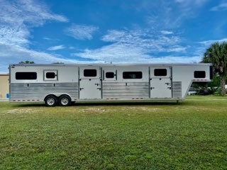 2021 Cimarron (6+1) Trailer with a Front Box Stall that has a drop gate over the neck, insulated roof, escape door, WERM FLOORING and a Side Ramp with Dutch Door.   The horse area has an interior height at 8' tall x 8'wide x 39' long,  escape door, drop down windows at the horses heads with drop down aluminum bars, insulated roof, roof vents, removable dividers, Airflow Center Gates, WERM FLOORING, Side & Rear Ramps with Dutch Doors.   Makes (4) Box Stalls