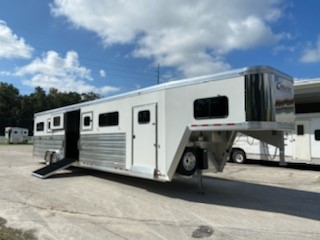 2021 Cimarron (6) horse head to head trailer with an interior height at 8' tall x 8' wide x 35' long, 6' tack room with saddle racks, bridle hooks, tack room window, brush box and a fold up step. The horse area has 6 stalls with one large center box, can be made into a 4 horse head to head or 3 box stalls. Has an escape door, drop down windows at the horses heads, insulated roof, roof vents, side ramp with dutch doors, rubber mats over all aluminum floor  and a rear ramp with dutch doors.