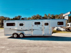 """2021 Cimarron (2+1) Trailer with a front tack room that has adjustable saddle racks, adjustable pad rack, bridle hooks, carpet lined wall, brush box and a walk thru door into the horse area. In the horse compartment you have an interior height at 7'6"""" tall x 7' wide, escape door with a drop down window and drop down aluminum bars, insulated roof, roof vents, side ramp with dutch door, airflow center gate, sliding divider making it easy to load a golf cart or make a box stall,"""