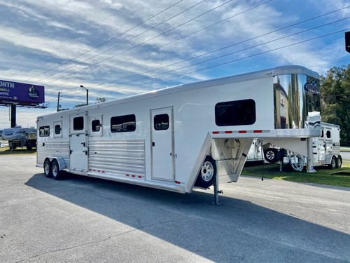 2021 Cimarron (4) horse head to head trailer with a 5' tack room that has saddle racks, bridle hooks, insulated roof, windows over the nose, sliding bus window in the tack room wall and a brush box. The horse area has an interior height at 8' tall x 7' wide, escape door, insulated roof, roof vents, drop down windows with drop down aluminum bars, rubber lined and insulated walls, Airflow on top