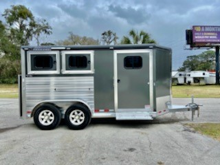 "2021 Cimarron (2) horse slant load bumper pull trailer with a ""Ready to Go Package"" tack room completely lined with Carpet, bridle hooks, water tank, hat shelf, cloth bar, battery box, spare tire and a door caddy.   The horse area has an interior height at 7' tall x 7' wide, escape door, drop down windows at the horses heads and hips, insulated roof, electric fans, rubber lined & insulated walls, WERM Flooring, rear collapsible tack room with double back rear doors and a rear ramp!"