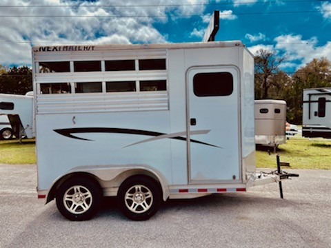 """2012 Nextrail (2) horse slant load bumper pull trailer with a front tack room that has (2) removable saddle racks, bridle hooks and a swinging tack room wall. The horse area has an interior height at 7'6"""" tall x 7' wide, escape door, roof vents, drop down windows at the horses heads, stock sided at the hips, rubber mats over wood floor and a full swinging rear door! Spare tire."""
