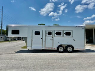 """2021 Cimarron (3) horse slant load trailer with a 6' tack room with the """"Ready to Go Package"""" consisting of a swing out saddle rack, bridle hooks, boot box, door caddy and a brush box. The horse area has an interior height at 8' tall x 8' wide, escape door, roof vents, electric fans, insulated roof, drop down windows at the horses heads and hips, rubber lined and insulated walls, air flow dividers with bottom dividers, rubber mats over all aluminum floor and a rear ramp with dutch doors!"""