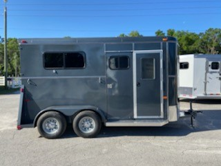 2021 Bee (2) horse straight load bumper pull trailer with a front tack room that has saddle racks, bridle hooks, and a spare tire.  The horse area has an interior height at 7' tall x 6' wide, (2) escape doors, sliding bus windows along the sides of each horse, removable dividers, rubber mats over wood floor and a rear ramp with dutch doors!  The exterior has two 3500lbs axles.  Charcoal in Color.