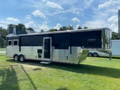 2016 Hart (2) horse living quarter with at 12' Trail Boss Conversion that has a huge bedroom over the nose with a King size mattress, cabinets and a TV.  The living room has two fold down couches that make into beds, convection oven, recessed (2) burner cooktop, sink, cabinets, 6cu fridge & freezer and a large bathroom.