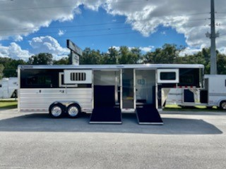 """2022 Cimarron (2+1) Trailer with a 5' front tack room that is insulated, has a drivers side access door, walk thru door and a curbside ramp with a dutch door.  The horse area has an interior height at 8'1"""" x 8' wide, escape door with a drop down window, side ramp with dutch doors, insulated roof, roof vents, drop down windows at the horses heads, removable Air Flow Center Gates, full Sliding Divider, rubber lined & insulated walls, WERM  Flooring and a rear ramp with dutch doors!"""